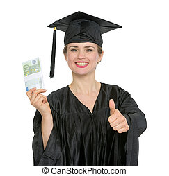 Smiling graduation student woman with pack of euros showing thumbs up. HQ photo. Not oversharpened. Not oversaturated