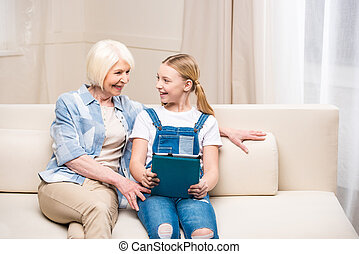 Smiling grandmother and granddaughter sitting on sofa with digital tablet and looking at each other