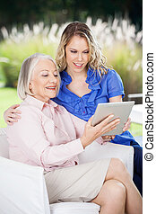 Smiling Grandmother And Granddaughter Using Tablet Computer