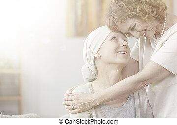 Smiling grandmother hugging sick woman