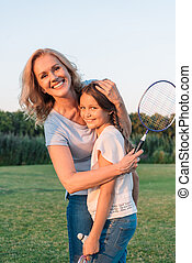 smiling grandmother hugging granddaughter