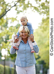 Smiling grandmother piggyback ride with baby
