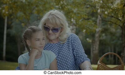 Smiling grandmother talking with cute girl in park -...