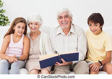 Smiling grandparents with grandchildren reading
