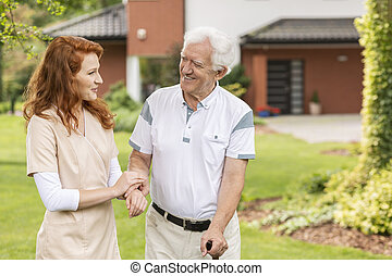 Smiling grey-haired senior man with a walking stick talking talking with a helpful caretaker in uniform in the garden of a assisted living home.