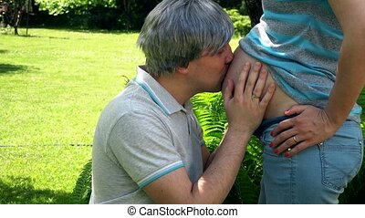 Smiling grey head man kissing belly of his pregnant woman and look at camera