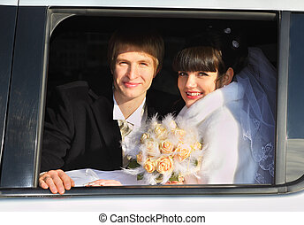 smiling groom and bride with bouquet sitting in limousine and looking out window at winter outdoors