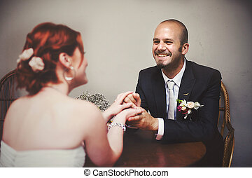 Smiling groom hodls bride's hands sitting at the wooden table