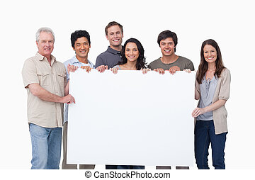 Smiling group holding blank sign together against a white background