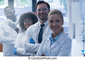 Smiling Group Of Scientists In Modern Laboratory With Female Leader, Mix Race Team Of Scientific Researchers In Lab