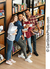 Smiling group of students standing in library make a selfie