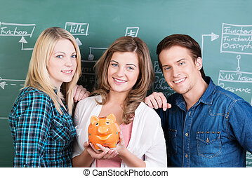 Smiling group of students with a piggy bank