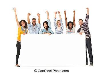 Smiling group of young friends showing large poster and...
