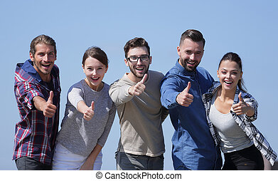 smiling group of young people showing thumb up.isolated on a...