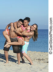 smiling group of youth, kids,or teenagers playing, piggyback on beach summer holiday