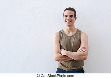 Smiling guy standing against white background with arms crossed