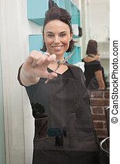 Smiling hairdresser holding hair scissors