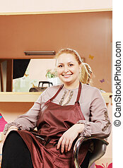 Smiling hairdresser in chair
