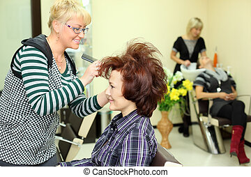 Smiling hairdresser makes hair styling for woman by rake-comb in beauty salon; focus on client; other barber washes second client head