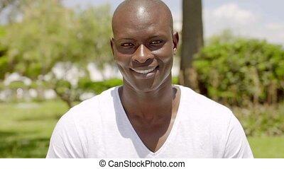 Smiling handsome bald black man in the park