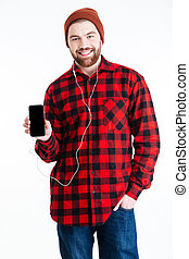 Smiling handsome bearded man showing smartphone with blank screen