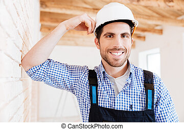 Smiling handsome builder standing near the wall