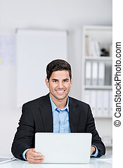 Smiling handsome businessman by the office