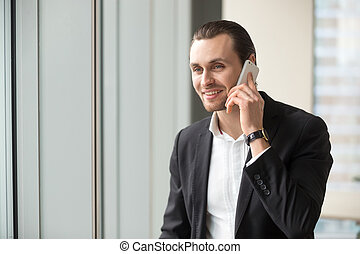 Smiling handsome businessman in suit talking on cellphone.