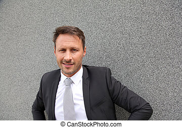 Smiling handsome businessman leaning on concrete wall