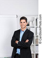 Smiling handsome businessman near a flip-chart