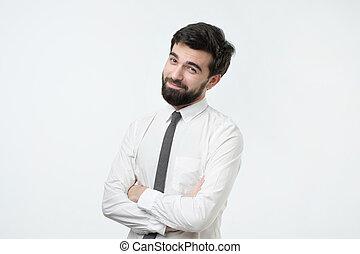 Smiling handsome hispanic man in white shirt crossing hands.