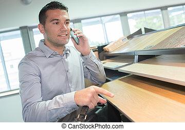 smiling handsome male designer using mobile phone in the studio