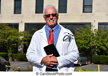 Smiling Handsome Male Doctor Wearing Lab Coat With Tablet At Hospital