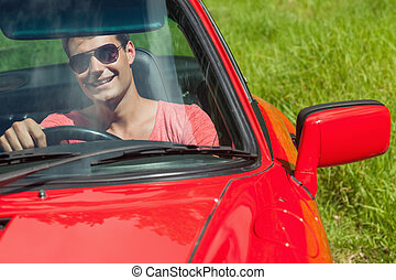 Smiling handsome man driving his cabriolet