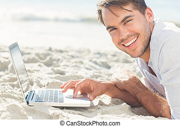 Smiling handsome man on the beach using his laptop