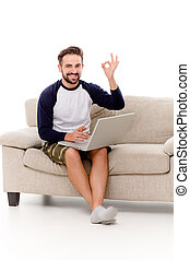 ??Smiling handsome man sitting on sofa with laptop on knees.