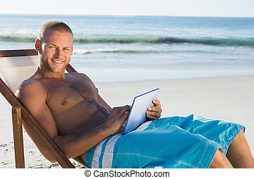 Smiling handsome man using his tablet while sunbathing