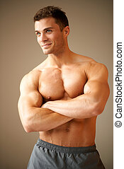 Smiling handsome man with muscular arms crossed looking his...