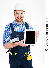 Smiling handsome young builder holding blank screen tablet