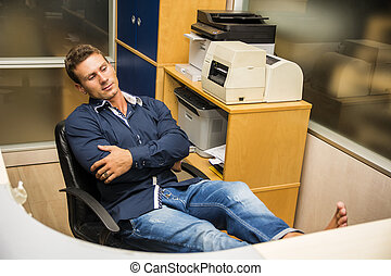 Smiling handsome young businessman sitting at desk in office