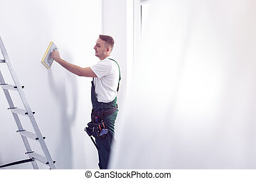 Smiling handyman cleaning white wall before painting while renovating interior