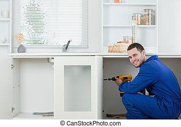 Smiling handyman fixing a door