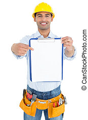 Smiling handyman in yellow hard hat pointing at clipboard -...