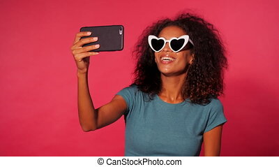 Smiling happy african american woman with curly hair in green t-shirt making selfie on smartphone over pink wall background. Girl in heart shaped sunglasses.