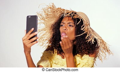 Smiling happy african american woman with curly hair yellow dress and straw hat making selfie on smartphone over white wall background. Girl having fun, builds faces, fooling around.