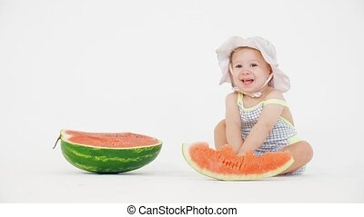 Smiling happy baby girl and sliced watermelon on white background