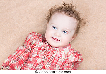 Smiling happy baby girl in a red dress
