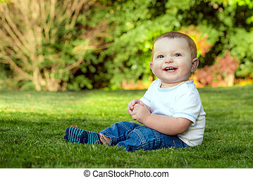 Smiling happy baby playing on the grass outdoors