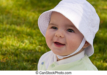Smiling happy baby wearing hat outdoors