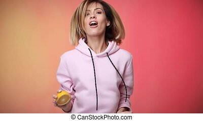 smiling happy blonde caucasian woman in casual pink clothes holding oranges and dancing on pink color background in studio.
